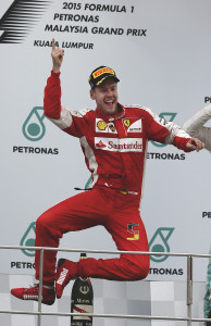 Ferrari driver Sebastian Vettel of Germany jumps on the podium as he celebrates after winning the Malaysian Formula One Grand Prix at Sepang International Circuit in Sepang, Malaysia, Sunday, March 29, 2015. (AP Photo/Andy Wong)