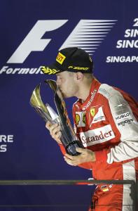 Ferrari driver Sebastian Vettel of Germany kisses the trophy on the podium after winning the Singapore Formula One Grand Prix on the Marina Bay City Circuit in Singapore, Sunday, Sept. 20, 2015. (AP Photo/Wong Maye-E)