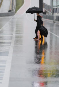 A Force India crew member walks across pit road as rain falls before the scheduled start of the third practice session for the Formula One U.S. Grand Prix auto race at the Circuit of the Americas, Saturday, Oct. 24, 2015, in Austin, Texas. (AP Photo/John Locher)
