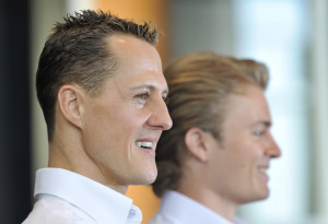 Mercedes Grand Prix driver Michael Schumacher of Germany, left, and teammate Nico Rosberg of Germany, right, pose for photographers before giving a news conference held at a Mercedes showroom in Manama, Bahrain, Thursday, March 11, 2010. The Bahrain Formula One Grand Prix will take place here on Sunday. (AP Photo/Gero Breloer)