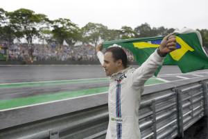 Williams driver Felipe Massa, of Brazil, walks along the track with a Brazilian flag after crashing during the Brazilian Formula One Grand Prix at the Interlagos race track in Sao Paulo, Brazil, Sunday, Nov. 13, 2016. Massa announces he will retire from Formula One after this season. (AP Photo/Leo Correa)
