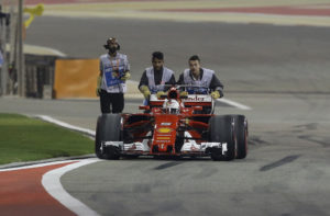 Ferrari driver Sebastian Vettel of Germany has his car pushed back to the pit lane during the second practice session for the Bahrain Formula One Grand Prix, at the Formula One Bahrain International Circuit in Sakhir, Bahrain, Friday, April 14, 2017. The Bahrain Formula One Grand Prix will take place on Sunday. (AP Photo/Luca Bruno)