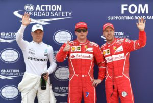 Ferrari's Finnish driver Kimi Raikkonen (C) celebrates after winning the pole position next to second placed Ferrari's German driver Sebastian Vettel (R) and third placed Mercedes' Finnish driver Valtteri Bottas after the qualifying session at the Monaco street circuit, on May 27, 2017 in Monaco, a day ahead of the Monaco Formula 1 Grand Prix. / AFP PHOTO / Andrej ISAKOVIC