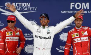 Mercedes' British driver Lewis Hamilton (C) celebrates after winning the pole position next to second placed Ferrari's Finnish driver Kimi Raikkonen (L) and third placed Ferrari's German driver Sebastian Vettel during the qualifying session at the Silverstone motor racing circuit in Silverstone, central England on July 15, 2017 ahead of the British Formula One Grand Prix. / AFP PHOTO / Andrej ISAKOVIC