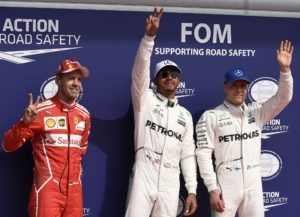 Mercedes' British driver Lewis Hamilton (C) celebrates winning the pole position next to second placed Ferrari's German driver Sebastian Vettel (L) and third placed Mercedes' Finnish driver Valtteri Bottas after the qualifying session at the Spa-Francorchamps circuit in Spa on August 26, 2017 ahead of the Belgian Formula One Grand Prix. / AFP PHOTO / JOHN THYS