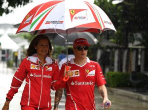 Ferrari's Finnish driver Kimi Raikkonen (R) walks under an umbrella in the paddock ahead of the Formula One Malaysia Grand Prix in Sepang on September 28, 2017. / AFP PHOTO / MANAN VATSYAYANA