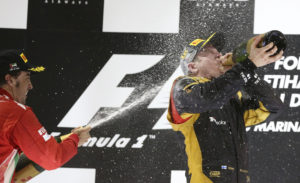 Lotus driver Kimi Raikkonen of Finland, winner, right, drinks rose water as second place Ferrari driver Fernando Alonso of Spain sprays him after the Emirates Formula One Grand Prix, at the Yas Marina racetrack, in Abu Dhabi, United Arab Emirates, Sunday, Nov. 4, 2012. (AP Photo/Luca Bruno)