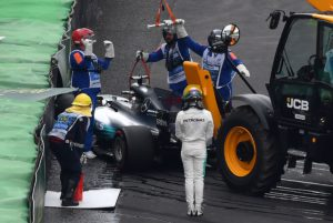 Mercedes' British driver Lewis Hamilton (in white) looks as his car is removed from the racetrack after crashing during the Brazilian Formula One Grand Prix Q1 qualifying session at the Interlagos circuit in Sao Paulo, Brazil, on November 11, 2017. / AFP PHOTO / Nelson ALMEIDA