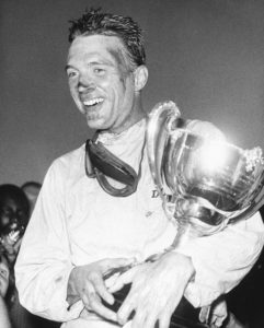 FILE - This Dec. 9, 1962 file photo shows Dan Gurney holding a trophy in Nassau, Bahamas. Gurney, the first driver to win in Formula One, IndyCar and NASCAR, died Sunday, Jan. 14, 2018 from complications of pneumonia. He was 86. His wife, Evi, announced his death in a statement distributed by All American Racers, Inc. (AP Photo)