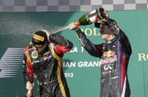 Lotus driver Kimi Raikkonen of Finland, left, is spayed with champagne by Red Bull driver Sebastian Vettel of Germany after the Australian Formula One Grand Prix at Albert Park in Melbourne, Australia, Sunday, March 17, 2013. Raikkonen won the race ahead of Ferrari driver Fernando Alonso of Spain in second and Vettel in third. (AP Photo/Rob Griffith)