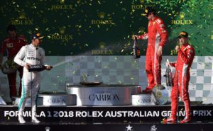 Ferrari's German driver Sebastian Vettel (R) celebrates winning the Formula One Australian Grand Prix with second-placed Mercedes' British driver Lewis Hamilton (L) and third-placed Ferrari's Finnish driver Kimi Raikkonen (C) in Melbourne on March 25, 2018. / AFP PHOTO / WILLIAM WEST / -- IMAGE RESTRICTED TO EDITORIAL USE - STRICTLY NO COMMERCIAL USE --