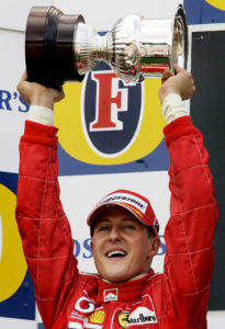 German Ferrari driver Michael Schumacher celebrates during the victory ceremony of the Belgian Formula One Grand Prix at the Spa-Francorchamps circuit, Sunday, Aug. 29, 2004, after finishing second place. McLaren driver Kimi Raikkonen won the race. Michael Schumacher clinched an unprecedented seventh Formula One drivers' title at the Belgian Grand Prix on Sunday. (AP Photo/Bas Czerwinski)