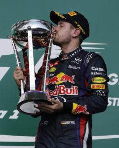 """FILE - In this Nov. 17, 2013 file photo, Red Bull driver Sebastian Vettel of Germany kisses his trophy after winning the Formula One U.S. Grand Prix auto race at the Circuit of the Americas in Austin, Texas. Formula One boss Bernie Ecclestone dismissed on Wednesday, Feb. 26, 2014, any clash between Formula One and NASCAR after the top executive at Texas Motor Speedway called F1 """"arrogant"""" for scheduling the United States Grand Prix in Austin on the same weekend that his track hosts NASCAR in Fort Worth. (AP Photo/Darron Cummings, File)"""
