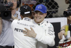 Mercedes driver Valtteri Bottas, of Finland, right, celebrates with his teammate Lewis Hamilton, of Britain, after setting the pole position during the qualifying session at the Yas Marina racetrack in Abu Dhabi, United Arab Emirates, Saturday, Nov. 25, 2017. The Emirates Formula One Grand Prix will take place on Sunday. (AP Photo/Luca Bruno)