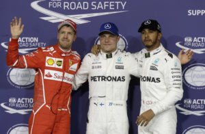 Mercedes driver Valtteri Bottas, center, of Finland, celebrates his pole position with his teammate second placed Lewis Hamilton, right, of Britain, and third placed Ferrari driver Sebastian Vettel, of Germany, during the qualifying session at the Yas Marina racetrack in Abu Dhabi, United Arab Emirates, Saturday, Nov. 25, 2017. The Emirates Formula One Grand Prix will take place on Sunday. (AP Photo/Luca Bruno)
