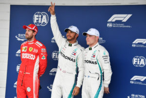 Mercedes' British driver Lewis Hamilton (C) celebrates after taking the pole position, next to Ferrari's German driver Sebastian Vettel (L) who took the second place and Mercedes' Finnish driver Valtteri Bottas (R) who took the third place, after the qualifying session for the F1 Brazil Grand Prix at the Interlagos racetrack in Sao Paulo, Brazil on November 10, 2018. (Photo by Nelson Almeida / AFP)