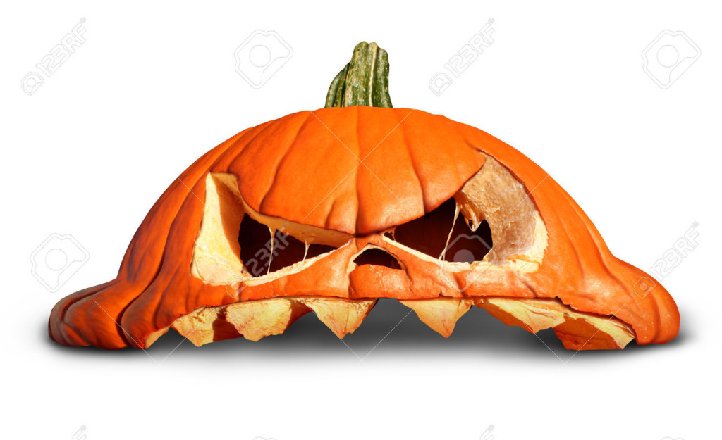 Pumpkin halloween as a broken smashed orange grinning jack o lantern symbol on a white background as an autumn concept.