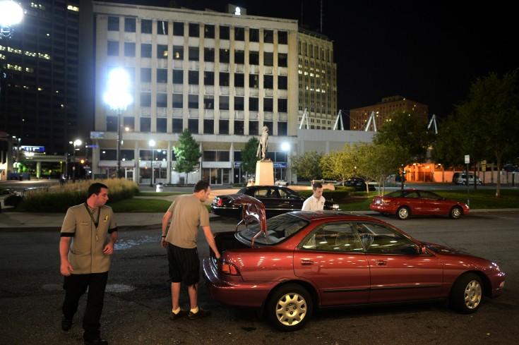 Nya gäster kommer till hotellet på Washington Boulevard. På andra sidan gatan står kontorshusen tomma och öde.
