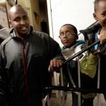 I trapphuset utanför kulturföreningen möter vi Farhan Ahmed, lokalvårdare inom kommunen, här med sonen Abdiqani och hans kusin Abduirman. Många är skeptiska till svenska medier, efter att lokaltidningen publicerat främlingsfientliga insändare.