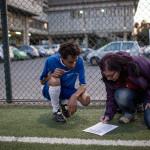 SNART STARTKLART. Daniela Conti och Yonatan Kasahun från Eritrea, en av de äldsta i laget, fyller i Liberi Nantes-spelarnas namn i matchformuläret strax före matchen mot polisstudenternas lag.