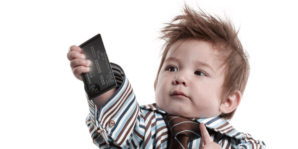 Boy (2-3) wearing oversized shirt and tie, holding credit card