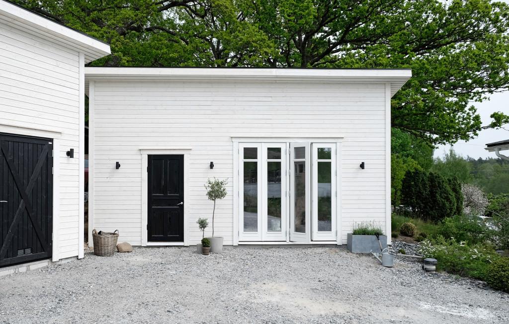 Den liggande vita panelen är grundmålad och ska få ytterligare ett lager vit färg i sommar. Dörrar och fönster är specialbeställda från Kronfönster i samma stil som bostadshuset. Den svarta dörren är en gammal innerdörr fyndad på Blocket som Andreas isolerat med ny panel på insidan. Utvändigt kvarstår även färdigställande av marken med stenläggning på den nya gårdsplanen.
