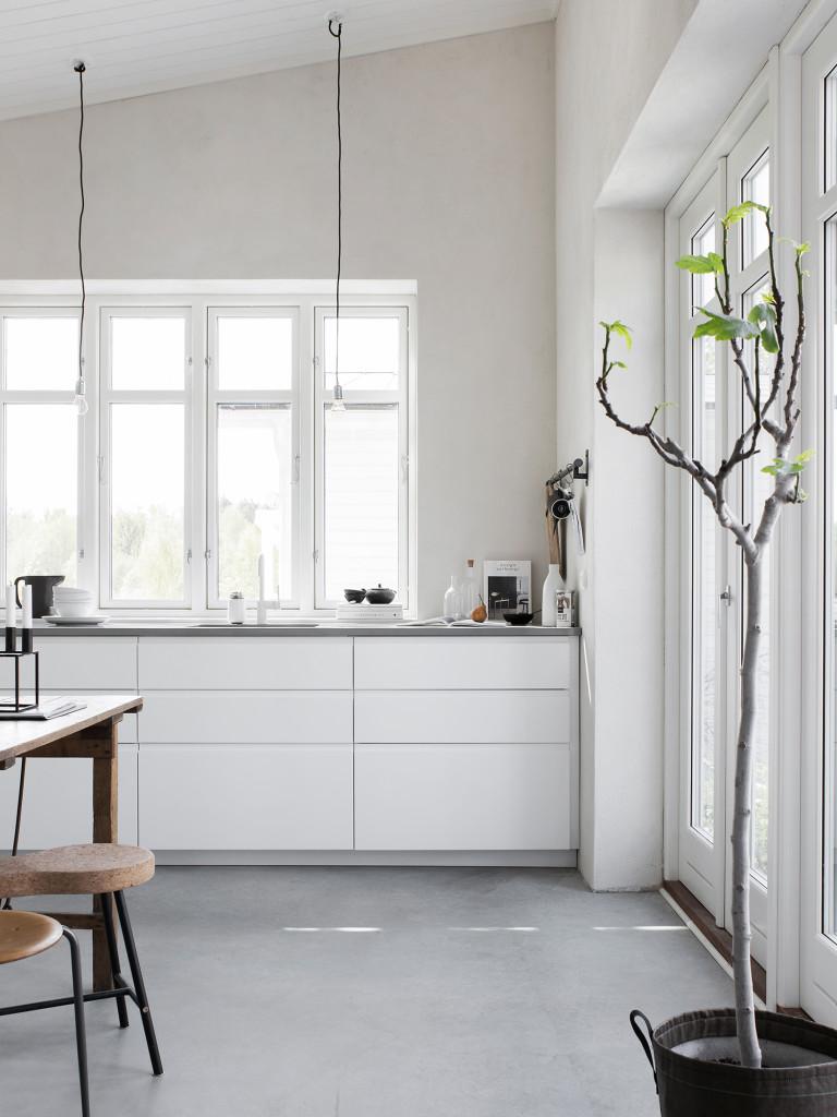 Köket är IKEAs Voxtorp med infällda grepplister för ett minimalistiskt uttryck. Bänkskivan i Silestone Cygnus från House of design. Lampor från Frama. Fikonträd i planteringssäck från Bacsac. Väggfärgen är Fresco kalkfärg i nyansen Bone från Pure & Original.