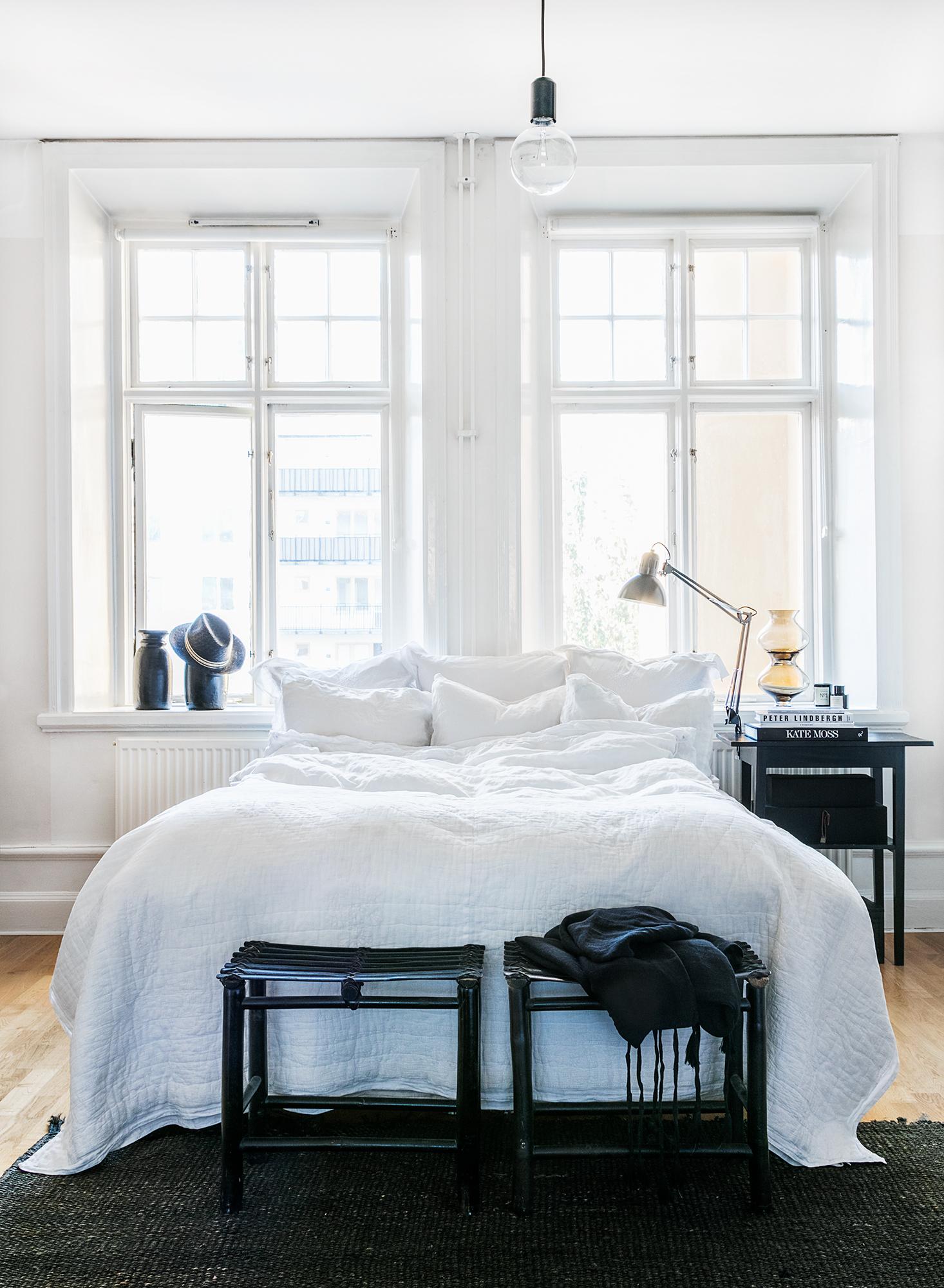 """Plats för vila. Marias säng är från Ikea med lakan i linne från H&M och stora kuddvar från DAY Home. """"Det finns inget bättre att sova i än skrynkliga krispiga linnelakan."""" Pallar från Housedoctor och sängbord/träurnor vintage. Rökfärgade glasvaser från Lene Bjerre."""