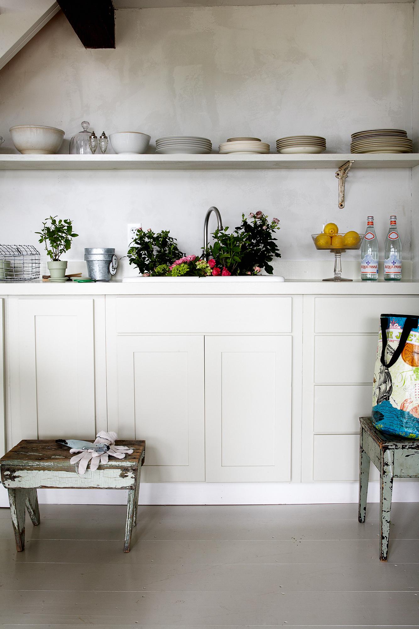 Köksinredningen är platsbyggd och lackerad i en milt grå ton, porslinet är udda från olika loppisar.