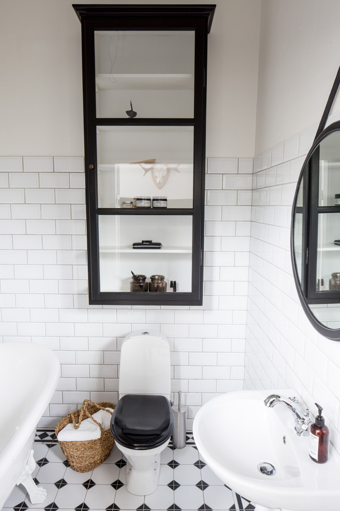 Även på gästtoaletten infinner sig harmoni med stramt vitt kakel i kontrast till inredningsdetaljer i svartaste svart.