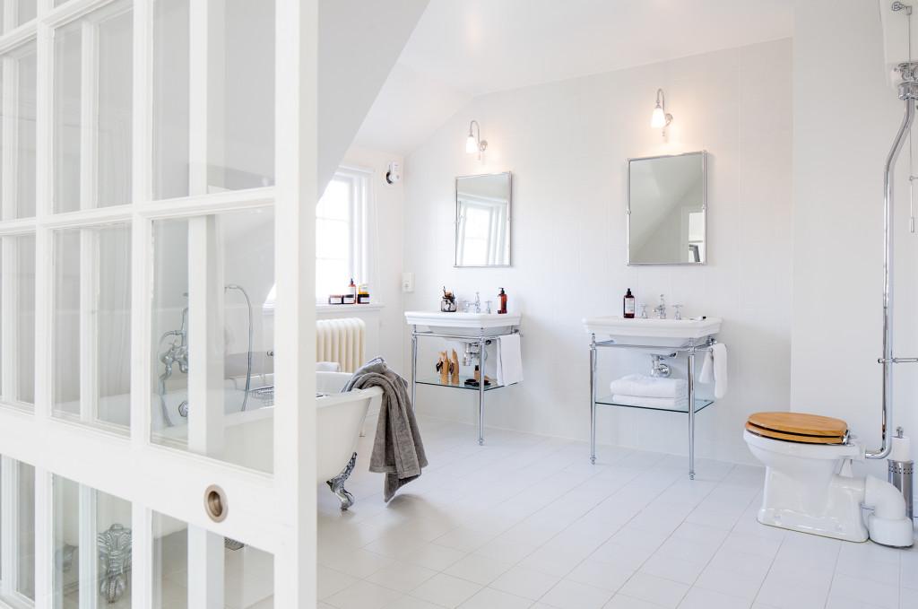 Badrummet är inrymt i en tidigare klädkammare och är som en balsal med golv av blänkande vita kakelplattor. Vaskar, badkar, toalettstol och kranar, alla från engelska Burlington. Sängborden i massivt trä är egen design.