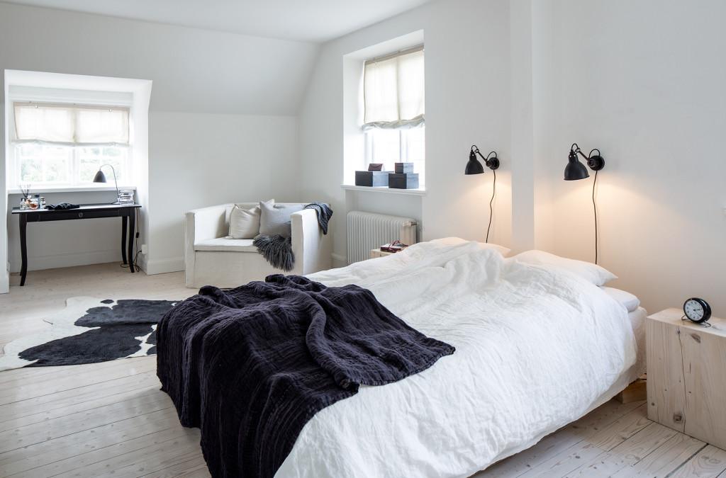 Bäddat för god sömn.  Lamporna är av märket Lampe Gras, fåtölj från TineK, svart skrivbord som fungerar som toalettbord är från Ikea. Sängborden är egen design.
