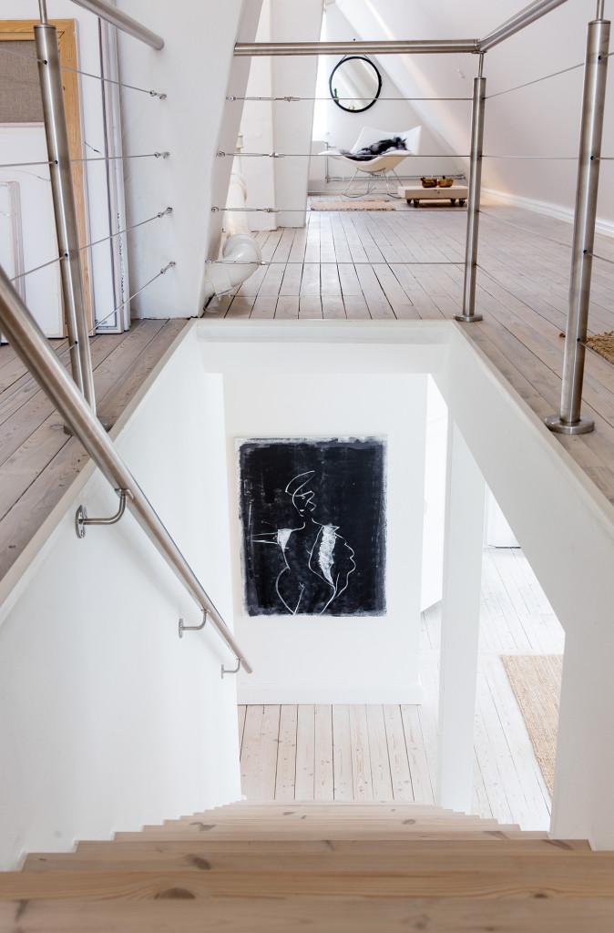 Råvinden förvandlades till gästavdelning och ateljé. Vyn från översta trappstegen ner mot plan två. Här hänger ett av Pias egna konstverk.
