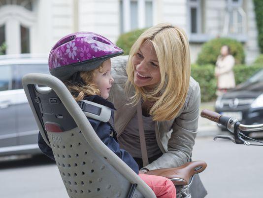 Mamma Carrie cyklar med sin unge till dagis (so very Berlin).