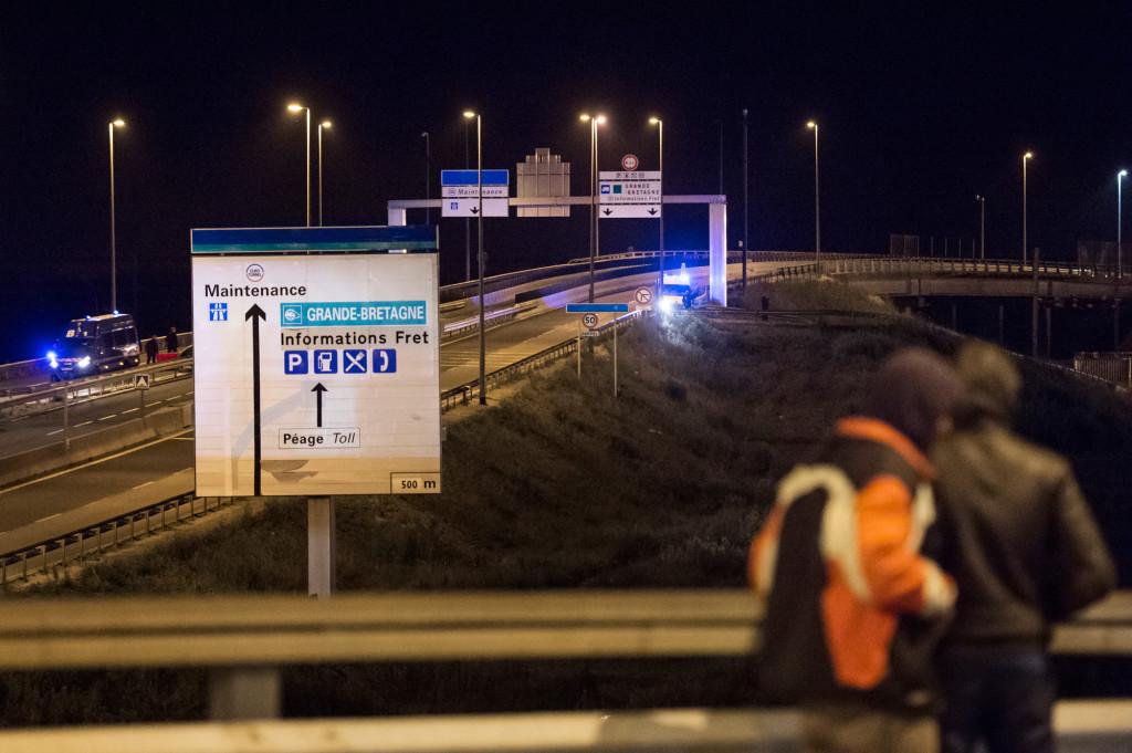 Fransk kravallpolis jagar bort migranterna som försöker ta sig upp på lastbilar som åker genom tunneln mot England.