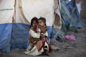 A girl holds her sister outside their tent at a camp for people displaced by recent fighting between government forces and Shi'ite rebels in the northwestern Yemeni city of Saada December 13, 2011. REUTERS/Khaled Abdullah