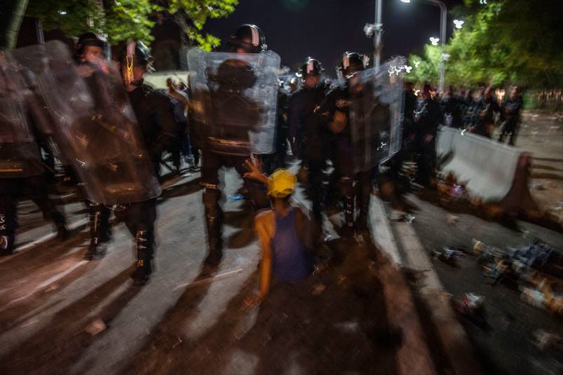 Ett 30-tal poliser omringar den ensamma 14-åriga pojken där han sitter på asfalten. Sedan för de bort honom. Foto: MAGNUS WENNMAN