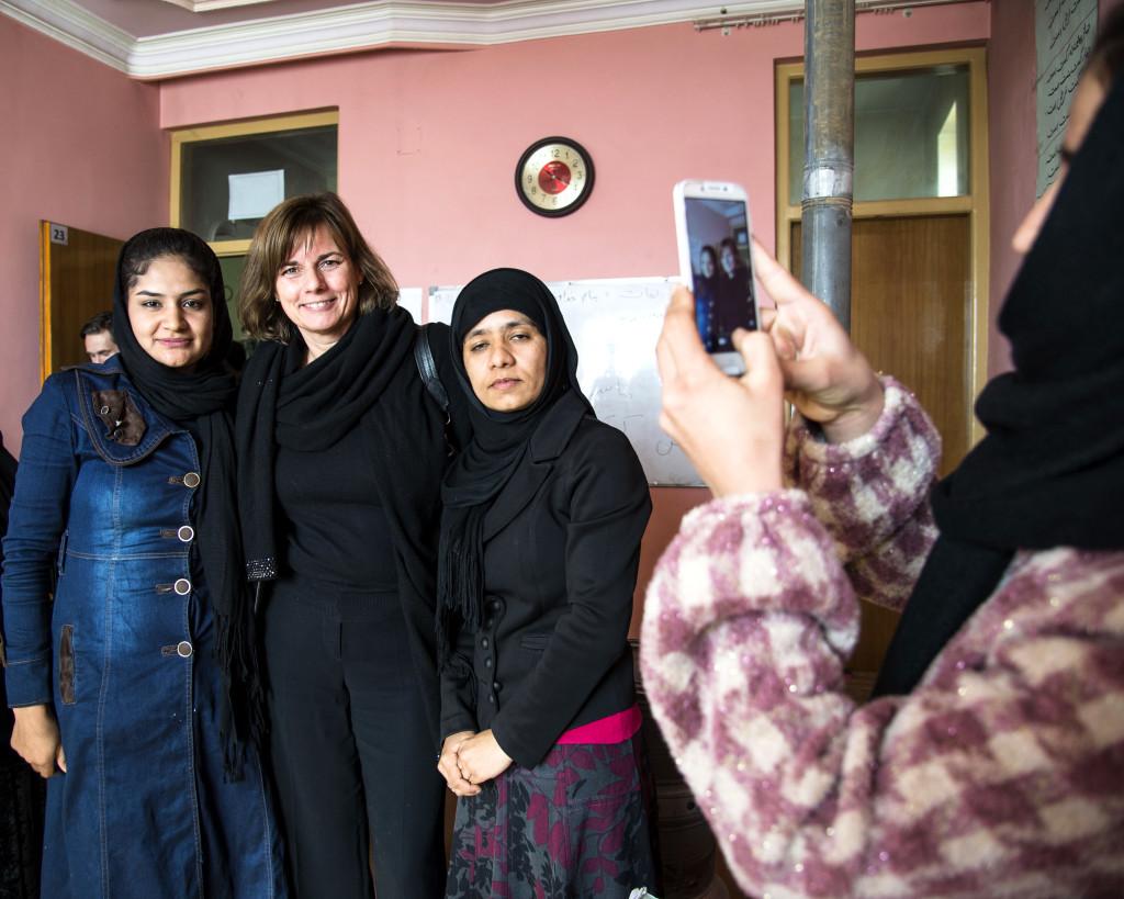 Anisa fotograferar klasskamraterna Zarifa (t.v) och Azada (t.h) med Isabella Lövin.