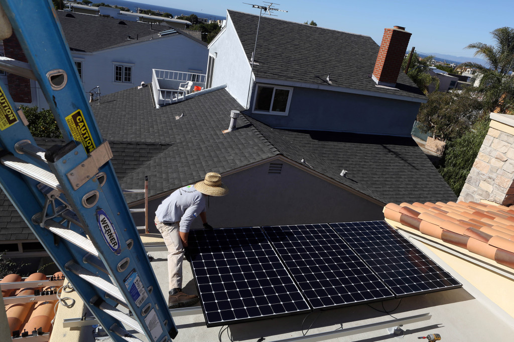 Kirk Mueller installerar solceller på ett hustak i Manhattan Beach.