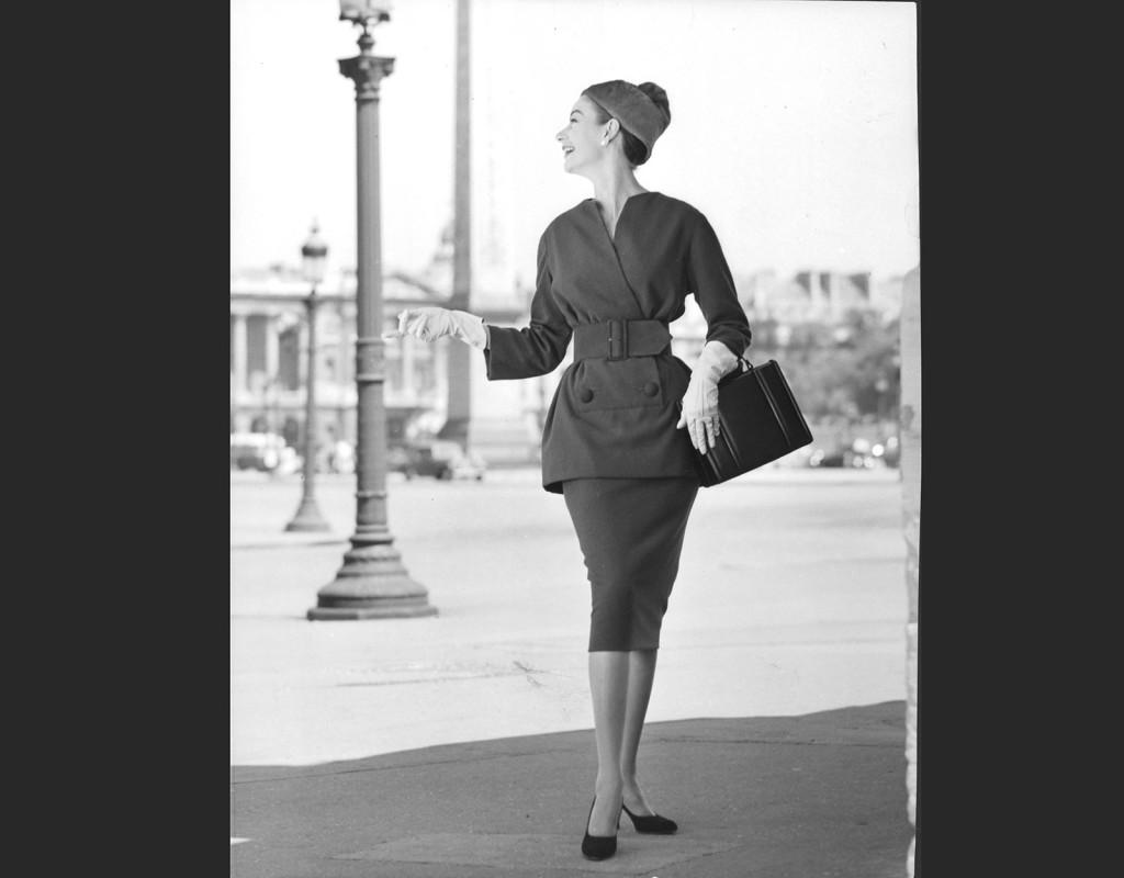 Den moderna 50-talskvinnan har välkammad knutfrisyr, pärlclips i öronen och dräkt med matchande handväska.