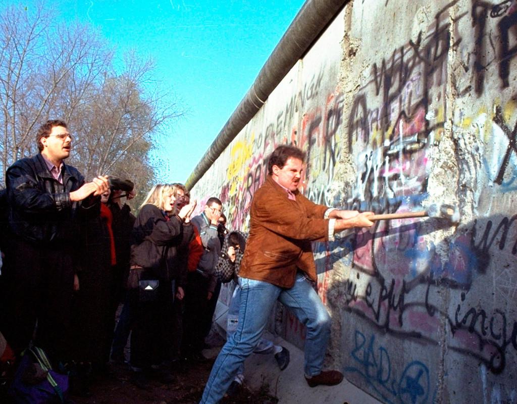 Berlinmuren rivs 1989 och världen jublar. En västberlinare slår med en slägga på muren vid Potsdamer Platz.  Foto: AP