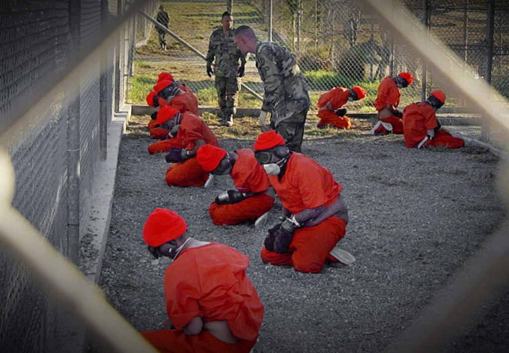ap foto : ap : ** file ** in this jan. 11, 2002 file photo, released by the department of defense, detainees wearing orange jump suits sit in a holding area as military police patrol during in-processing at the temporary detention facility camp x-ray on guantanamo bay u.s. naval base in cuba.  (ap photo/u.s. navy, shane t.mccoy, file) a jan. 11, 2002 file photo - released by the department of defense ap provides access to this publicly distributed handout photo to be used only to illustrate news reporting or commentary on the facts or events depicted in this image guantanamo politic automatarkiverad