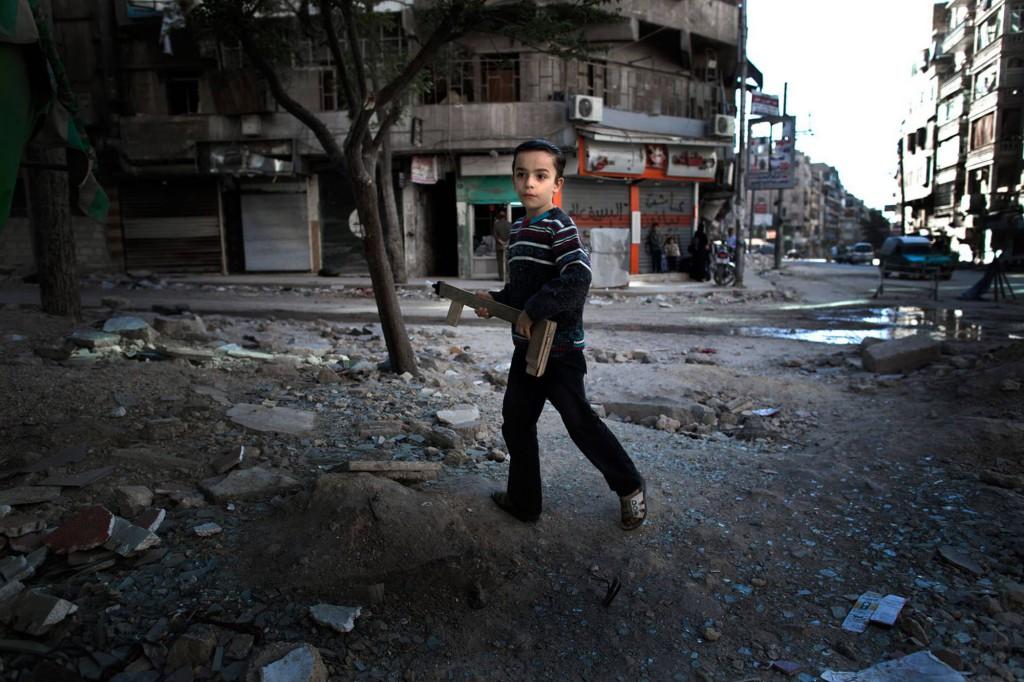 En ung pojke leker med ett hemmagjort leksaksgevär i Aleppo. Foto: NICLAS HAMMARSTRÖM