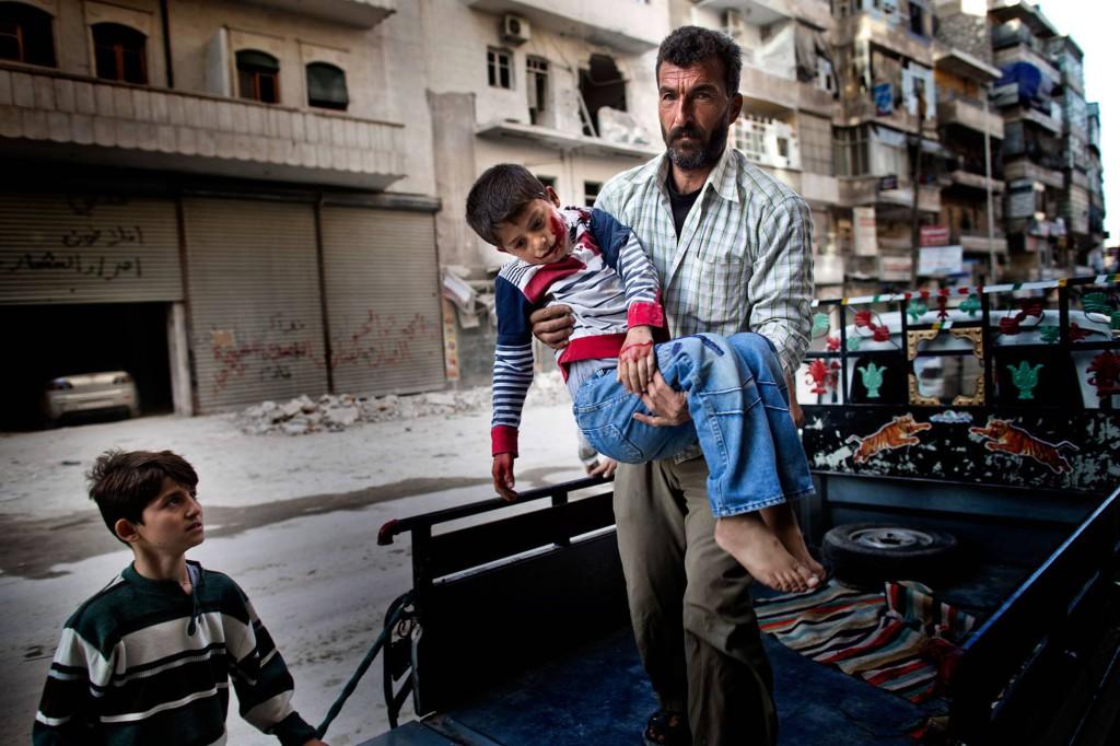 Sexårige Mustafa bärs in på sjukhuset av sin far. Mustafa var ute och lekte med sin kusin när han träffades av splitter från en granat. Foto: NICLAS HAMMARSTRÖM