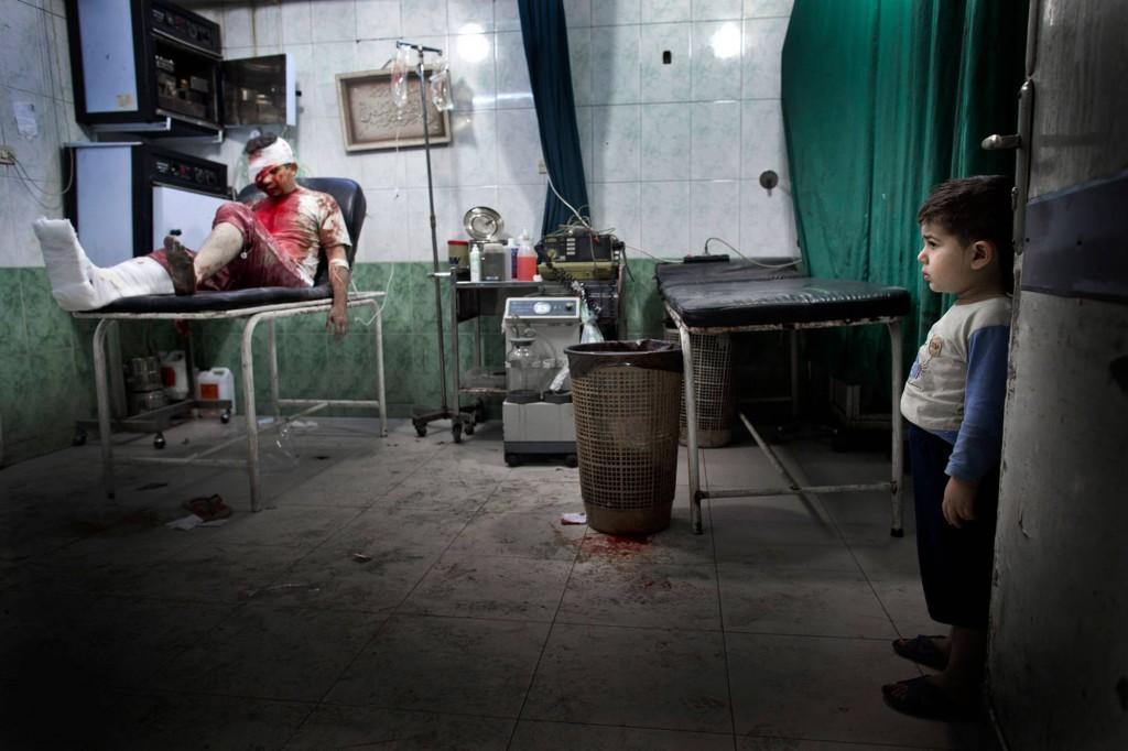 En liten pojke tittar på en skadad man i en av sjukhusets operationssalar. Foto: NICLAS HAMMARSTRÖM
