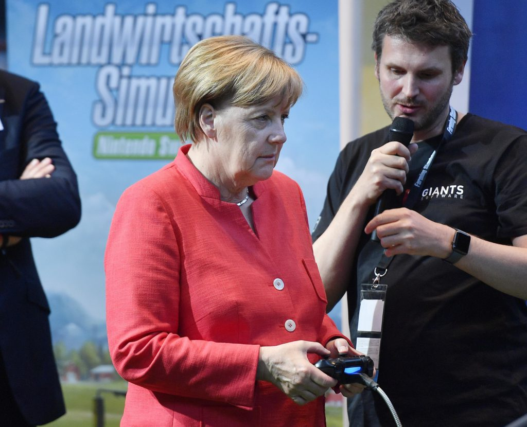 German chancellor Angela Merkel plays an agriculture simulation game during the Gamescom fair for computer games in Cologne, Germany, Tuesday, Aug. 22, 2017. The leading European trade fair for digital gaming culture is the meeting point for global companies from the entertainment industry and the international gaming community. (AP Photo/Martin Meissner)