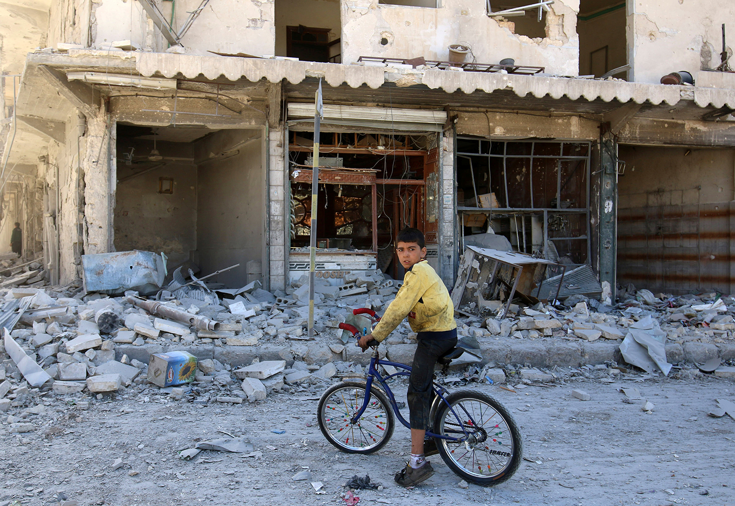 ALEPPO 2016-09-25 A boy sits on a bicycle in front of damaged shops after an airstrike on the rebel held al-Qaterji neighbourhood of Aleppo, Syria September 25, 2016. REUTERS/Abdalrhman Ismail Photo: / REUTERS / TT / kod 72000