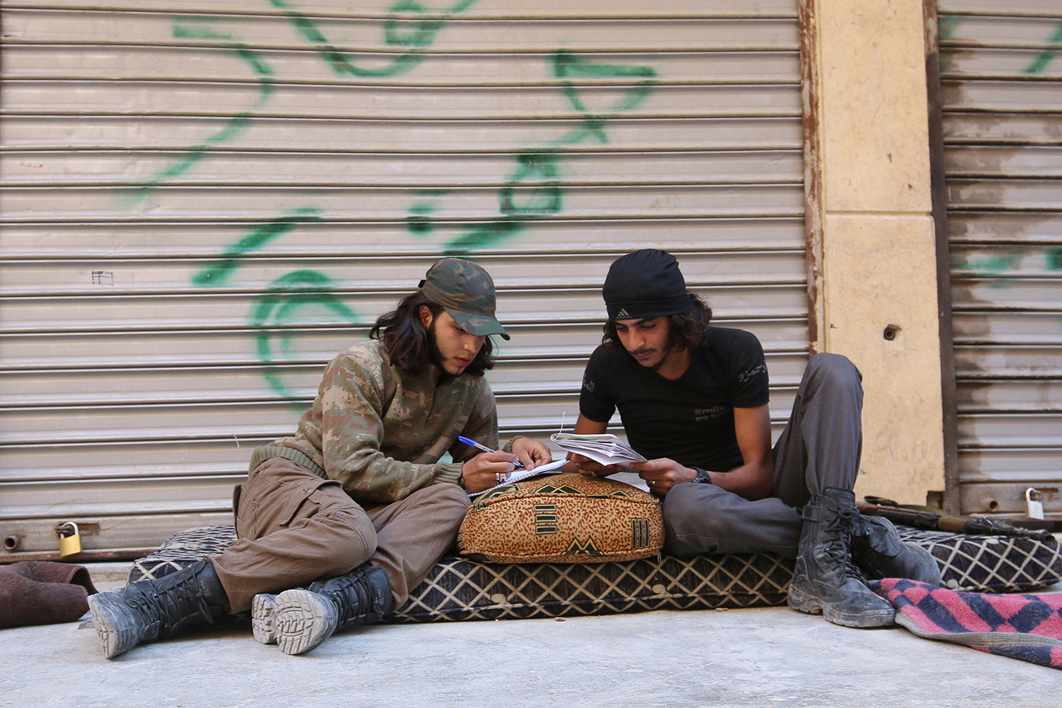 ALEPPO 2016-09-27 A Free Syrian Army fighter writes on a notebook as he sits with his fellow fighter in the rebel-held al-Myassar neighbourhood of Aleppo, Syria, September 27, 2016. REUTERS/Abdalrhman Ismail Photo: / REUTERS / TT / kod 72000