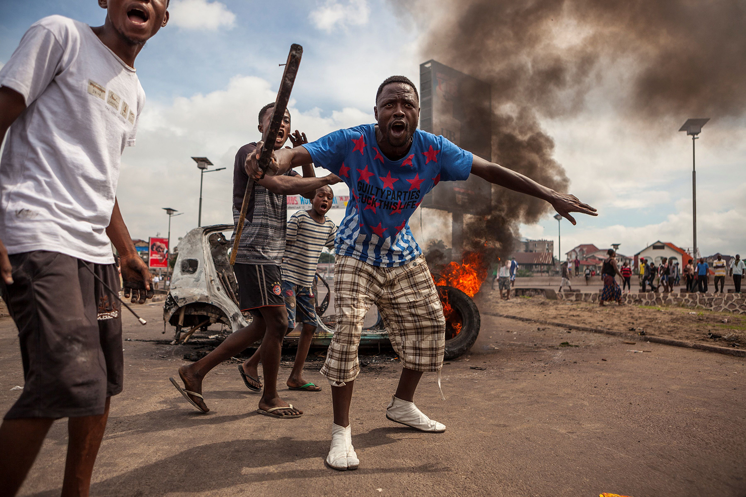 TOPSHOT - Demonstrators gather in front of a burning car during an opposition rally in Kinshasa on September 19, 2016. Police fired tear gas at scores of opposition supporters rallying in Kinshasa to demand that DR Congo's long-serving President Joseph Kabila step down this year, AFP journalists said. Kabila, who has ruled DR Congo since 2001, is banned under the constitution from running again -- but he has given no sign of intending to give up his job in December. / AFP PHOTO / EDUARDO SOTERAS / TT / kod 444