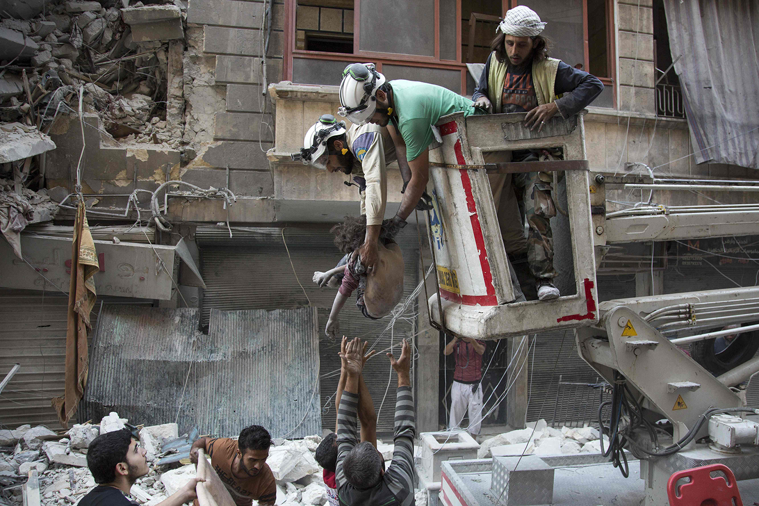 TOPSHOT - Syrian rescuers hand the body of a girl down to civilians on the ground after she was pulled from rubble of a budling following government forces air strikes in the rebel held neighbourhood of Al-Shaar in Aleppo on September 27, 2016. Syria's army took control of a rebel-held district in central Aleppo, after days of heavy air strikes that have killed dozens and sparked allegations of war crimes. / AFP PHOTO / KARAM AL-MASRI / TT / kod 444